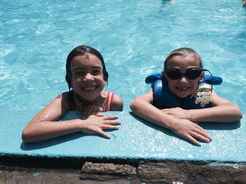 two kids smiling and bathing in the roxboro pool