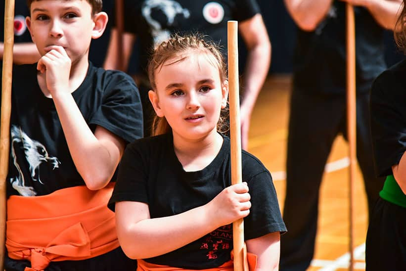 A Young girl holding a stick during kung fu class
